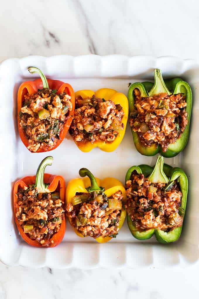 A baking dish showing colorful bell peppers stuffed with a turkey and rice mixture.