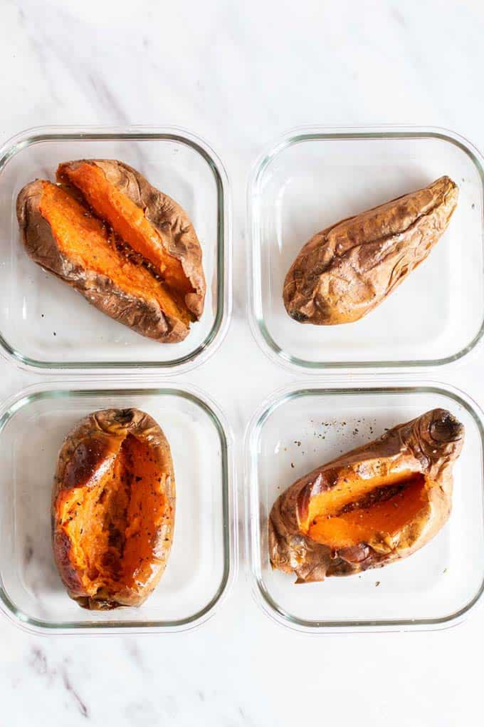 4 Baked sweet potatoes in meal prep containers.