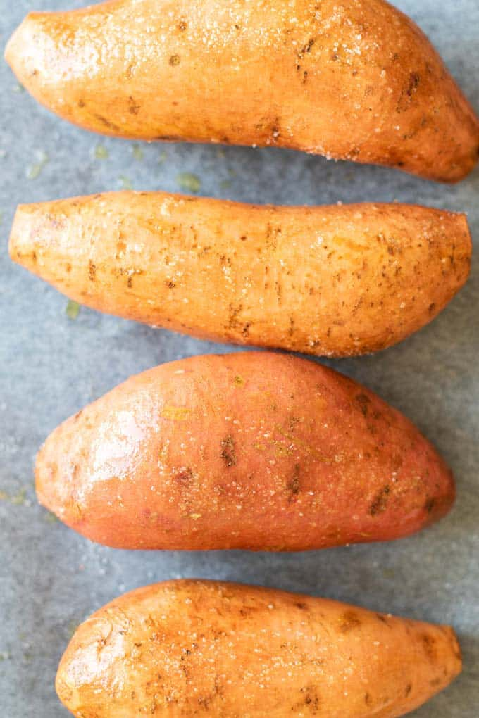 A close up of sweet potatoes rubbed with salt ready to be baked.