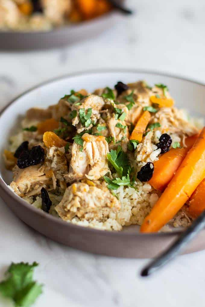 A close up of crockpot moroccan chicken served on cauliflower rice.
