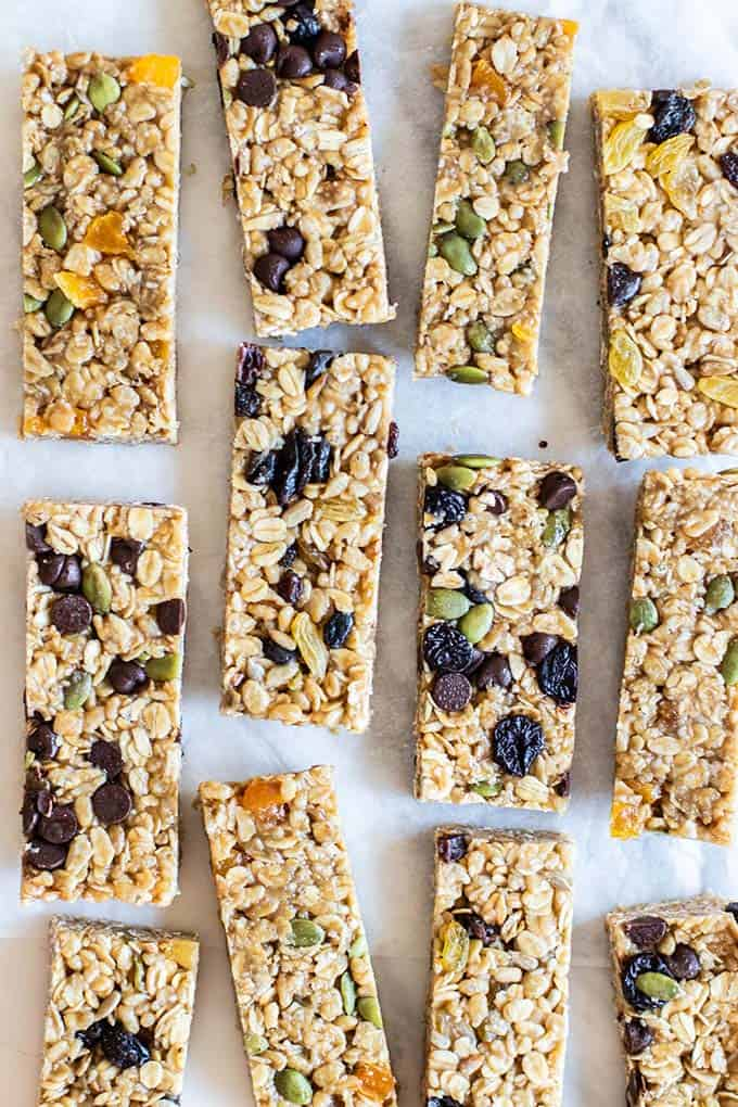 Assorted gluten free granola bars laid out on parchment paper.