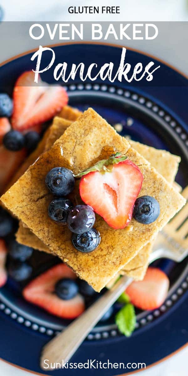 A close up image showing the baked pancakes served with berries and maple syrup.