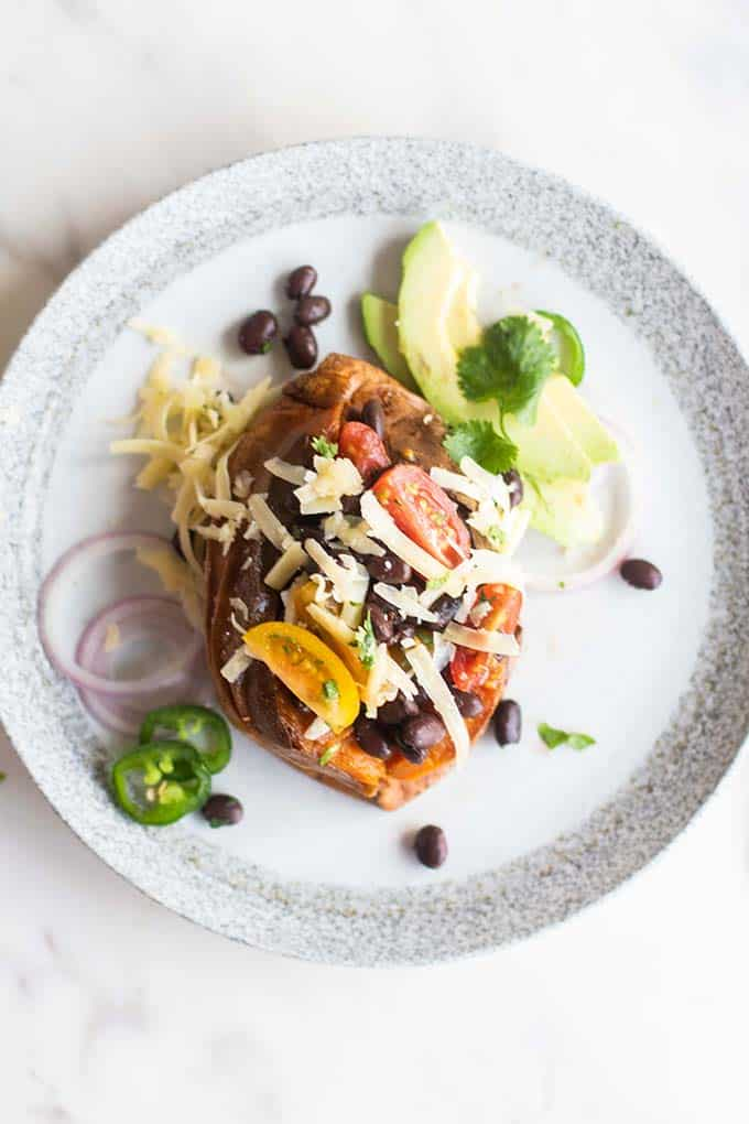 A sweet potato stuffed with black beans, cheese, and avocado.