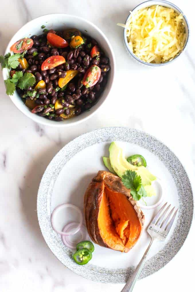 A baked sweet potato on a plate with a bowl of black beans with tomatoes and cilantro.