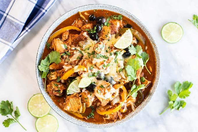 A dish showing crockpot enchilada chicken garnished with limes, cheese, and cilantro.