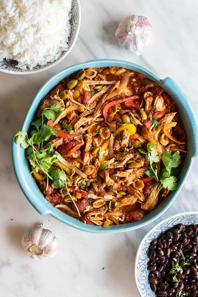 How to serve ropa vieja, showing side dishes of rice and black beans.