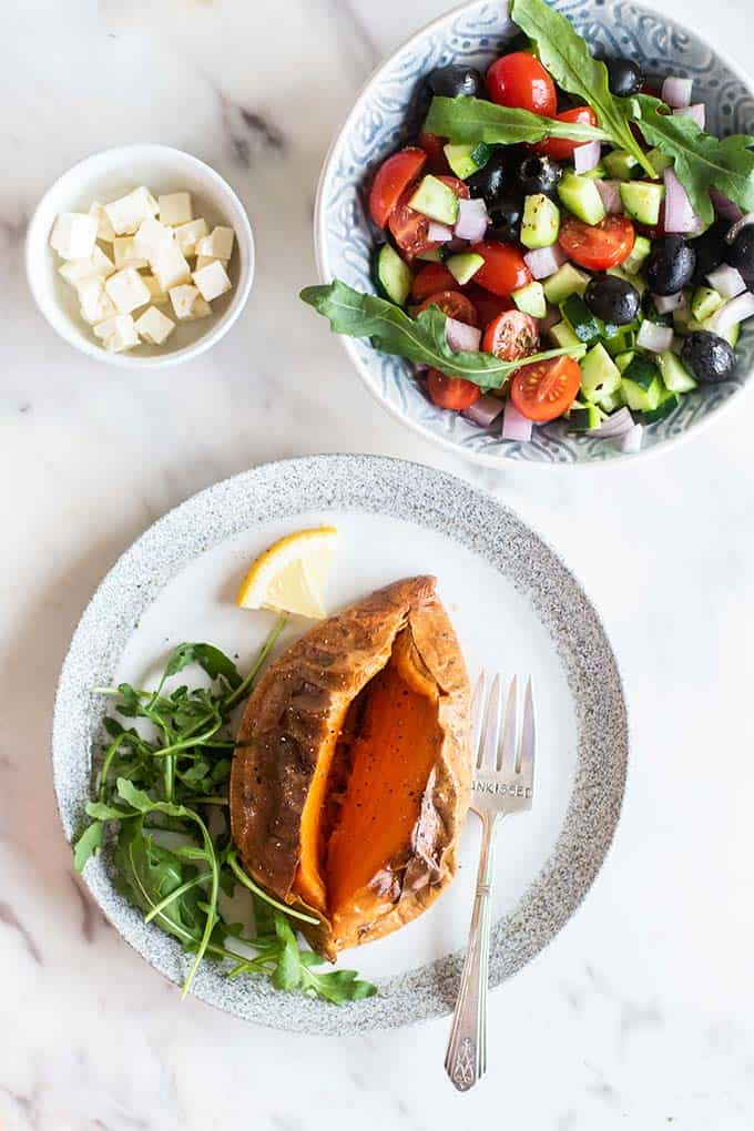 A baked sweet potato on a plate with a bowl of greek salad.