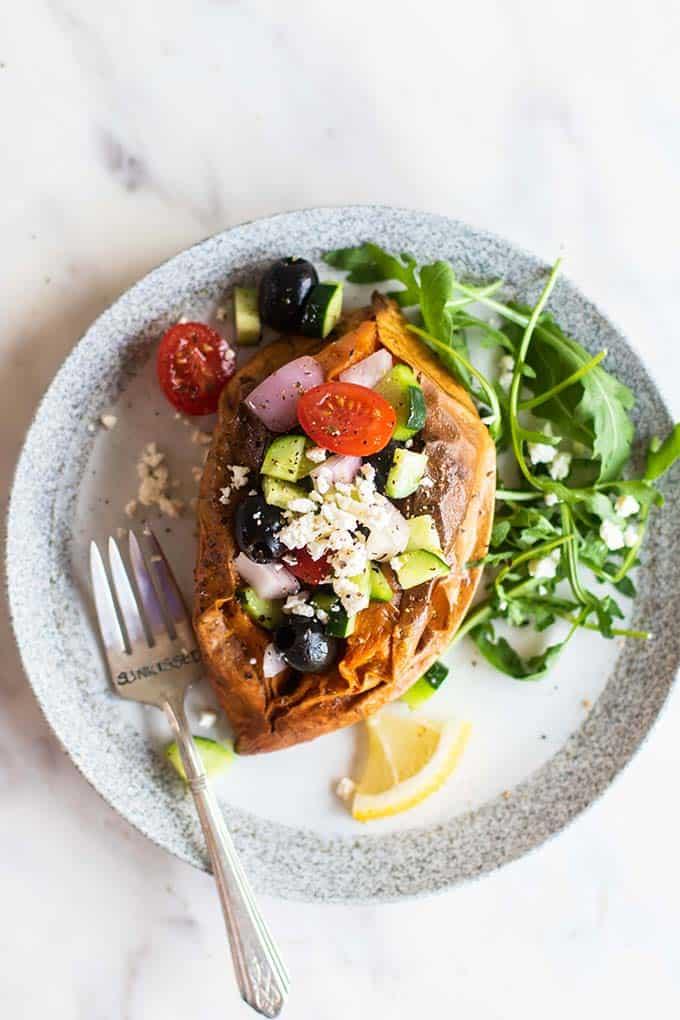 A baked sweet potato stuffed with greek salad.