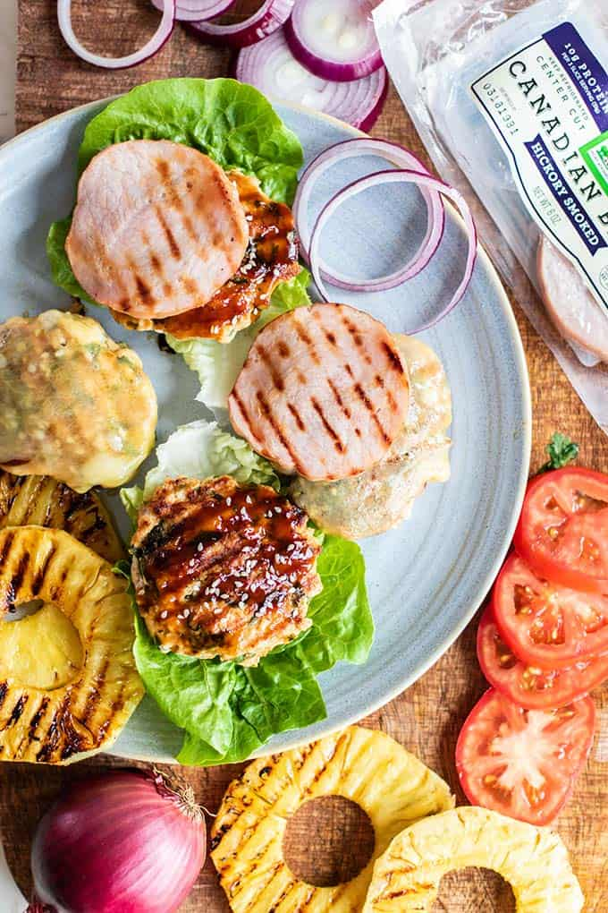 Grilled burgers, pineapple, and canadian bacon, with tomatoes, lettuce, and onions.