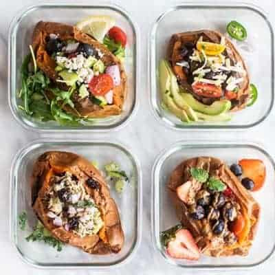 Four stuffed sweet potatoes in meal prep containers ready for the week.