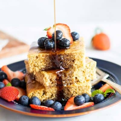 A stack of pancake squares topped with berries, being drizzled with maple syrup.