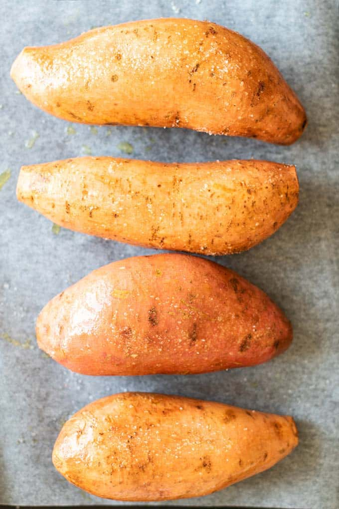 Raw sweet potatoes rubbed with salt and oil on a baking tray.