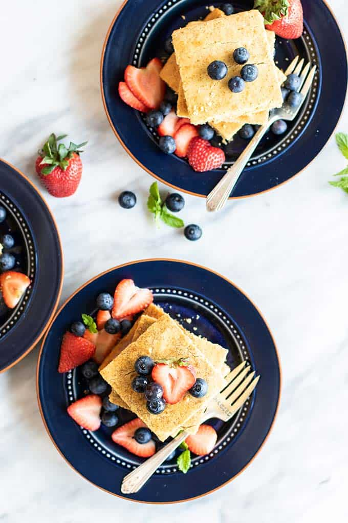 3 plates with stacks of baked pancakes and berries.