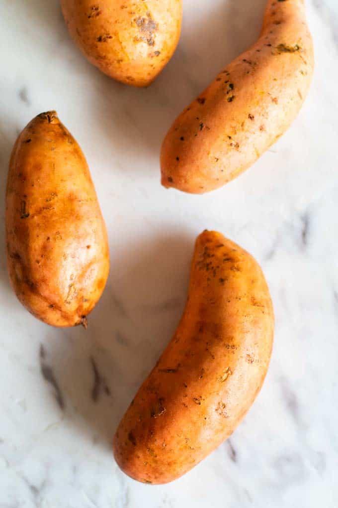 4 sweet potatoes being prepared to bake.
