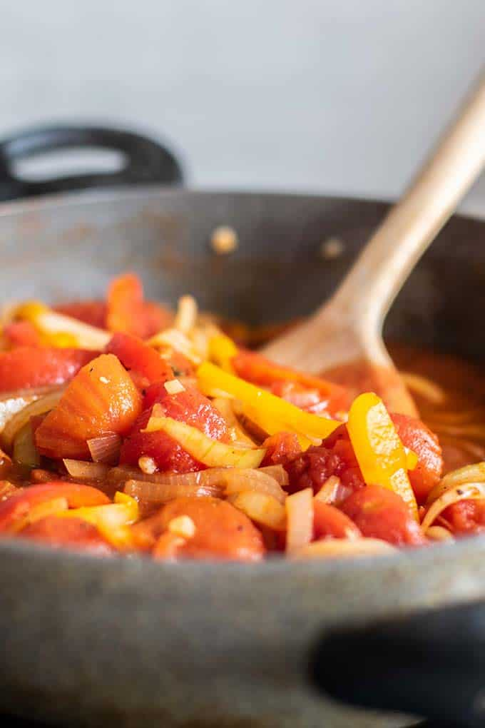 A pan with sauteed onions, peppers, and tomatoes.
