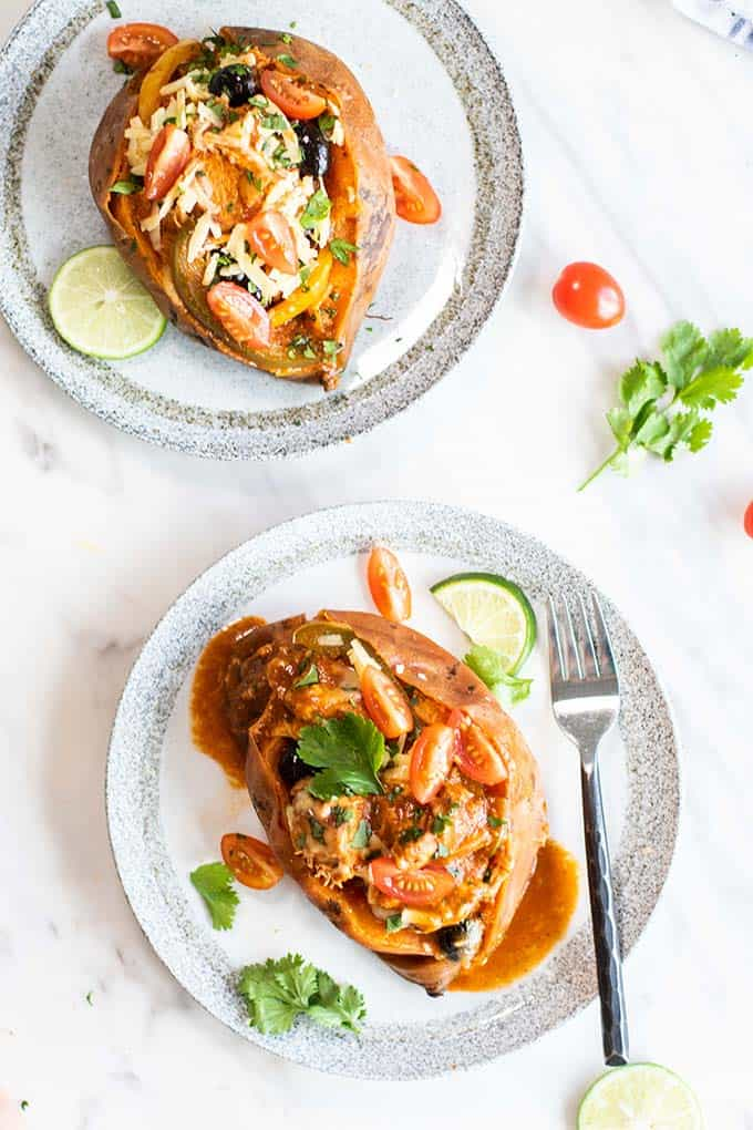 Two plates with baked sweet potatoes filled with chicken enchilada mixture.