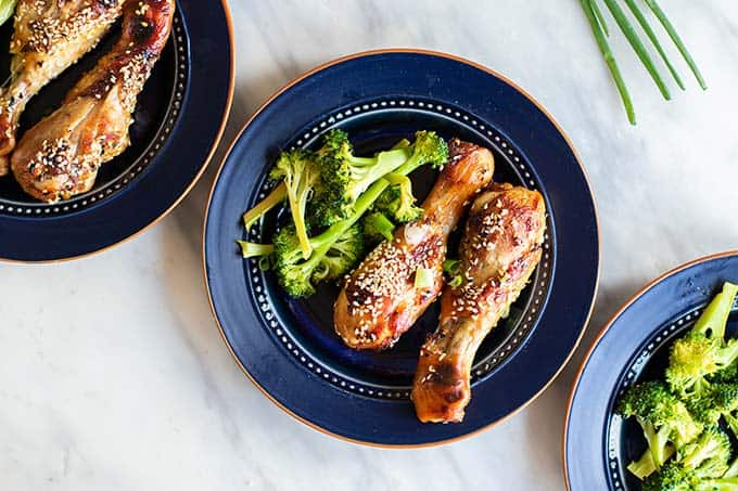Oven baked chicken legs served on a blue plate with broccoli.