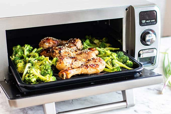 A pan coming out of the oven with chicken drumsticks and broccoli.