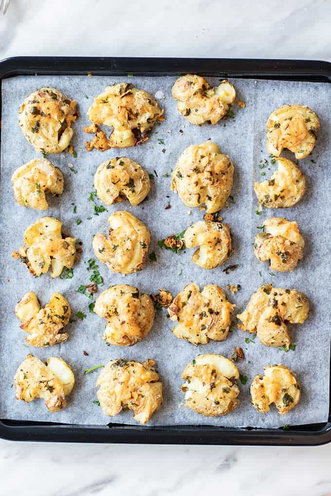 A baking tray with smashed potatoes in rows.