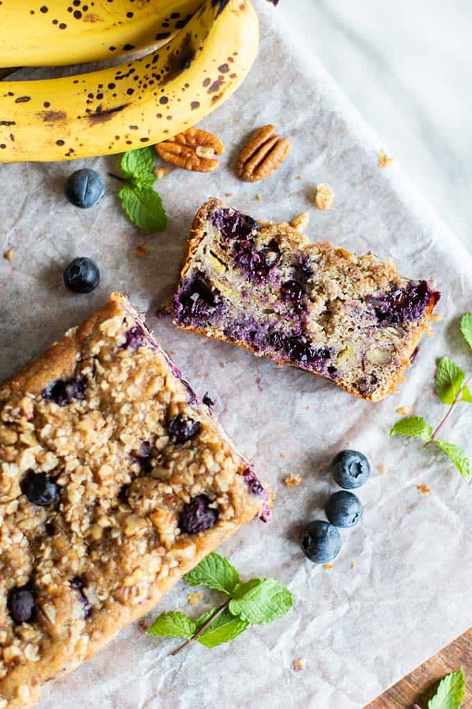 A loaf of blueberry pecan banana bread with a slice cut off.