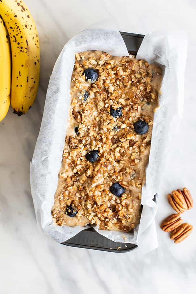 A loaf pan filled with blueberry pecan banana bread batter.