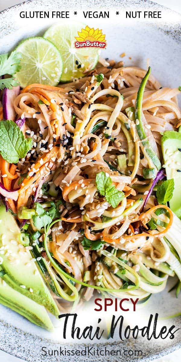 A close up view of a thai noodles dish with julienne zucchini, carrots and cabbage.