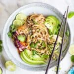 A spicy thai noodles dish garnished with avocado, sesame seeds and limes.