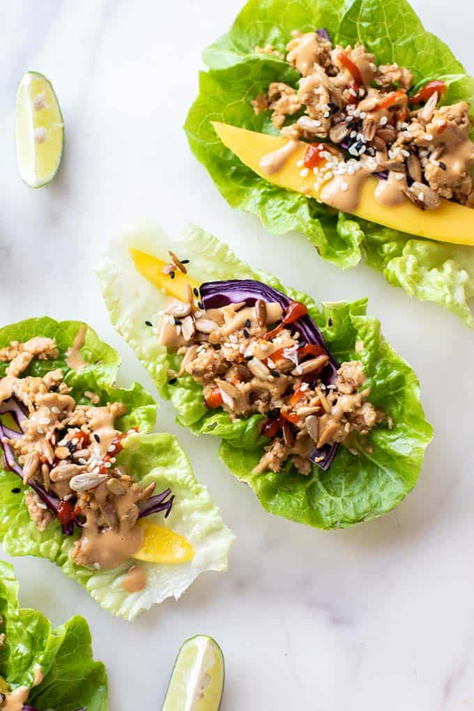 A close up of Thai chicken lettuce wraps garnished with cilantro and sesame seeds.