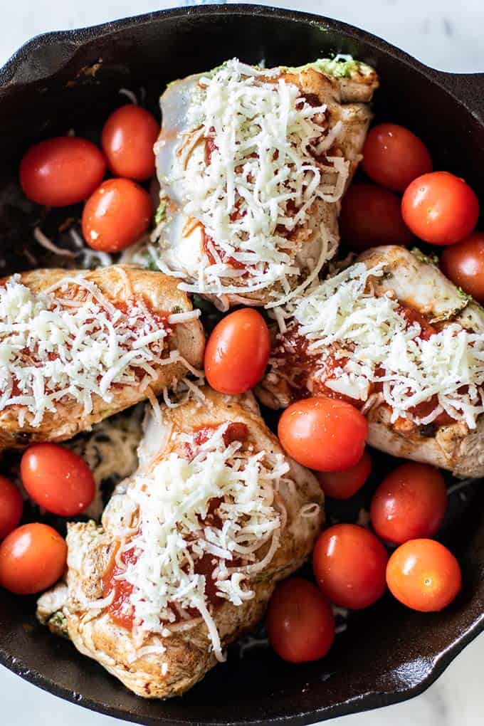 A cast iron pan with stuffed chicken breasts topped with pizza sauce and mozzarella cheese.