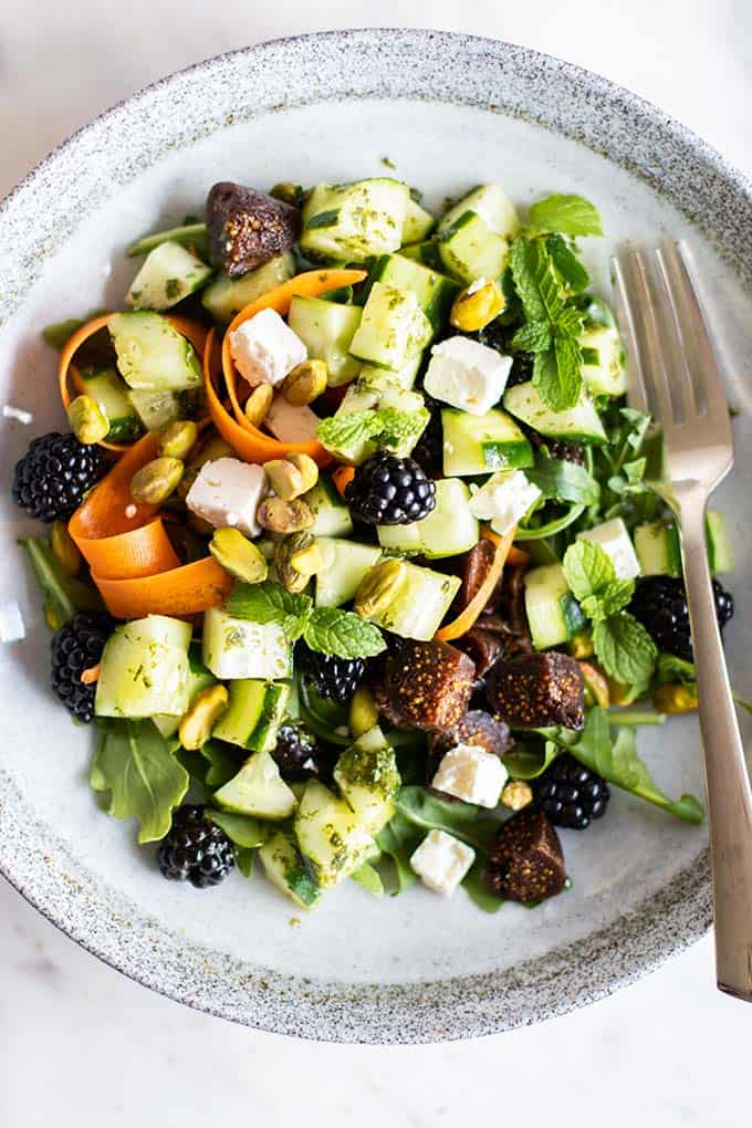 A blackberry fig salad garnished with feta cheese and pistachios.
