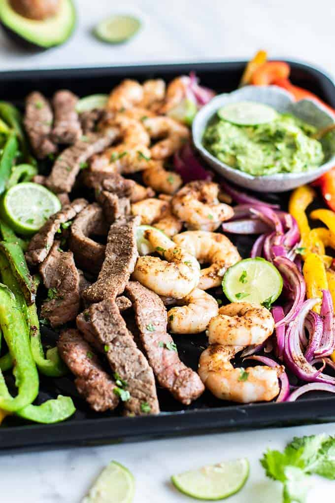 A side angle view of baked beef and shrimp fajitas.