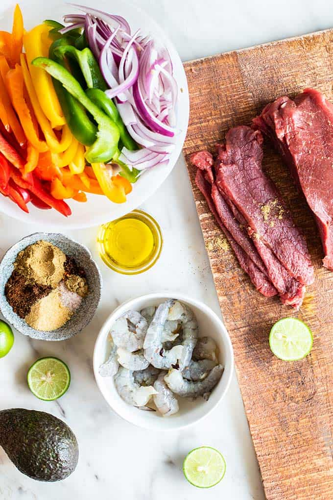 A top down view of all the ingredients needed for beef and shrimp fajitas, including colorful peppers and onions, spices, and meat.