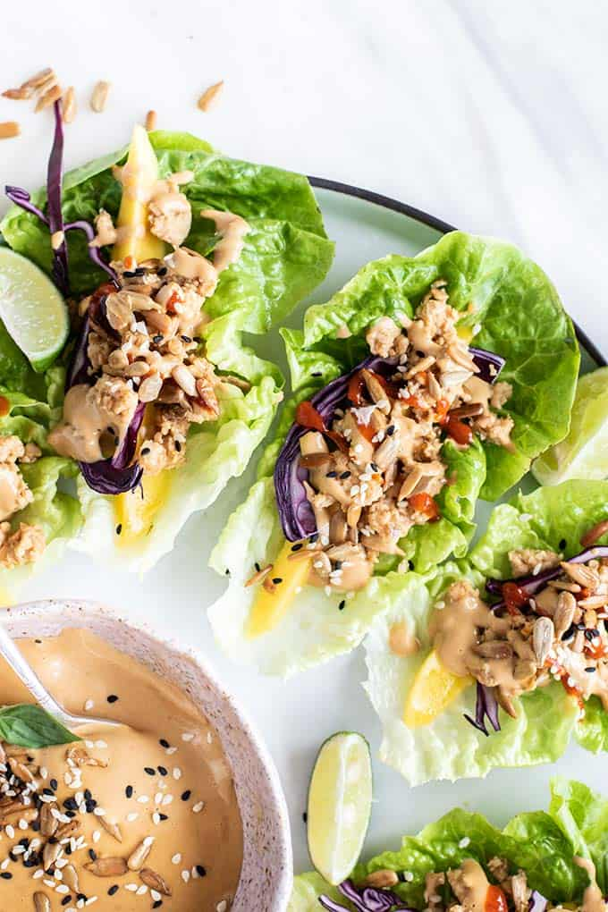 A close up of Thai chicken lettuce wraps next to a pink bowl of SunButter dipping sauce.
