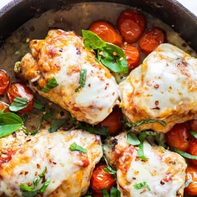 Stuffed chicken breasts garnished with basil and roasted tomatoes.