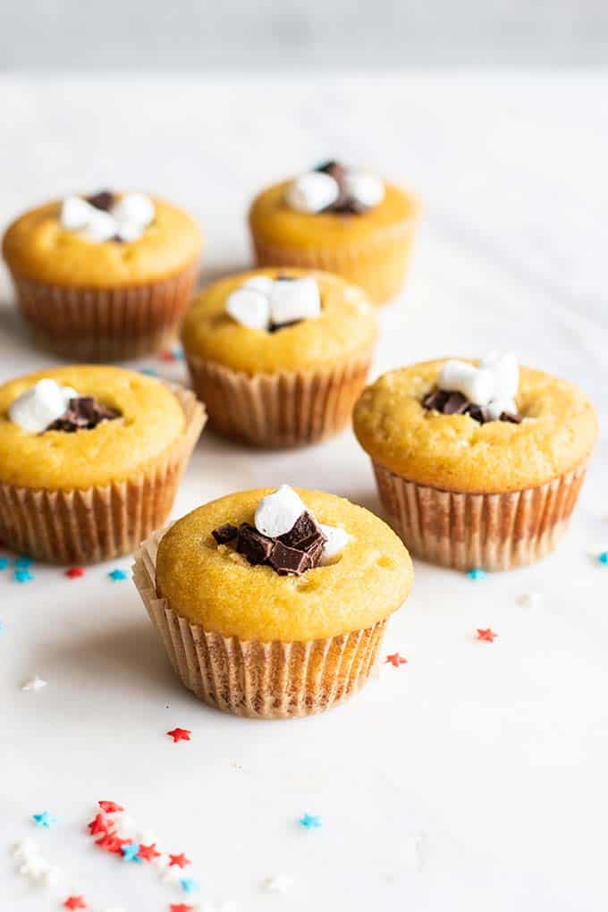 Cupcakes with a hole cut into the center, filled with marshallows and dark chocolate chunks.