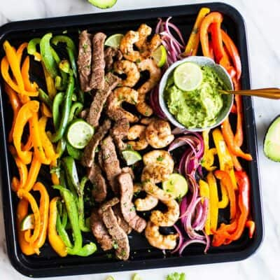 A top view of a sheet pan with colorful peppers, onions, steak and shrimp, tossed in a fajita seasoning.