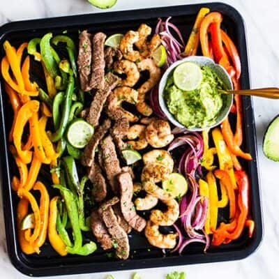 A view of the colored peppers, onions, steak and shrimp in this healthy sheet pan fajita recipe.