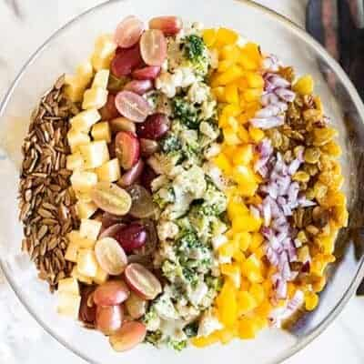 A top down view of a broccoli and cauliflower salad with rows of colorful toppings.