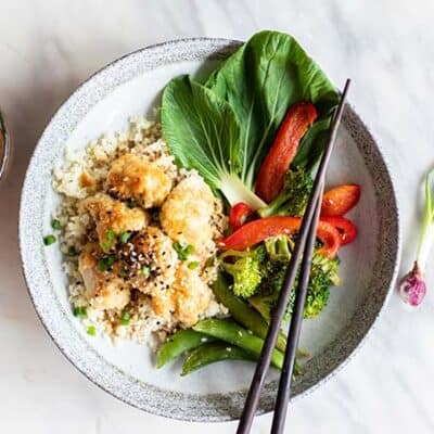 A white plate with cauliflower rice, gluten free sweet and sour chicken, and baked vegetables.