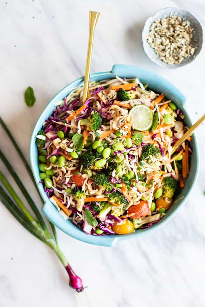 A bright and colorful Asian Cabbage Salad with Broccoli in a blue dish.