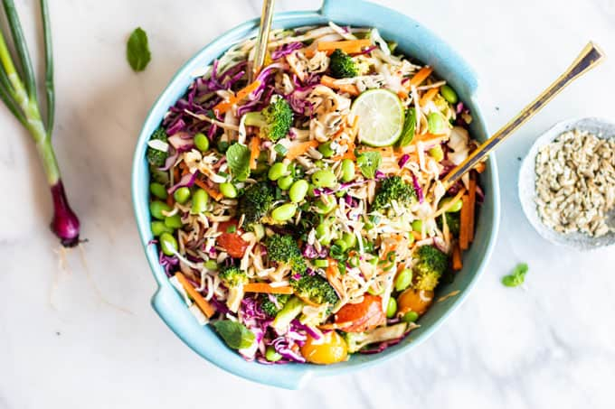 A bright and colorful Asian Cabbage slaw with Broccoli in a blue dish.