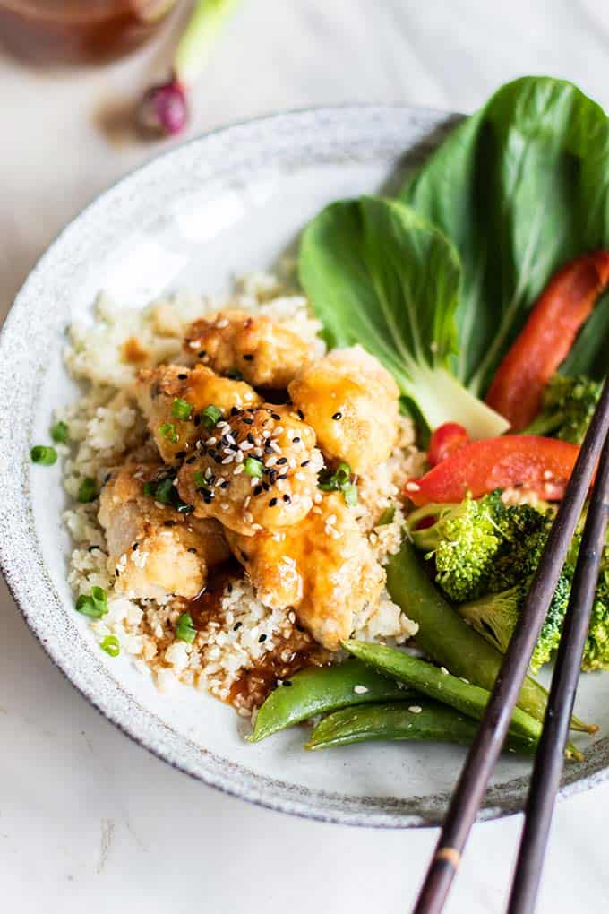 A close up of healthy sweet and sour chicken on a plate with bright veggies.