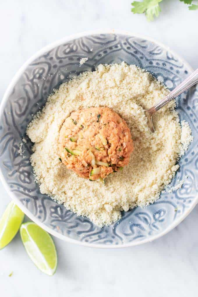 A salmon patty formed and in a bowl of almond flour.