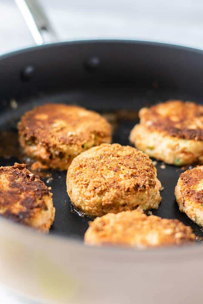 Salmon patties shown frying in a skillet until golden brown.