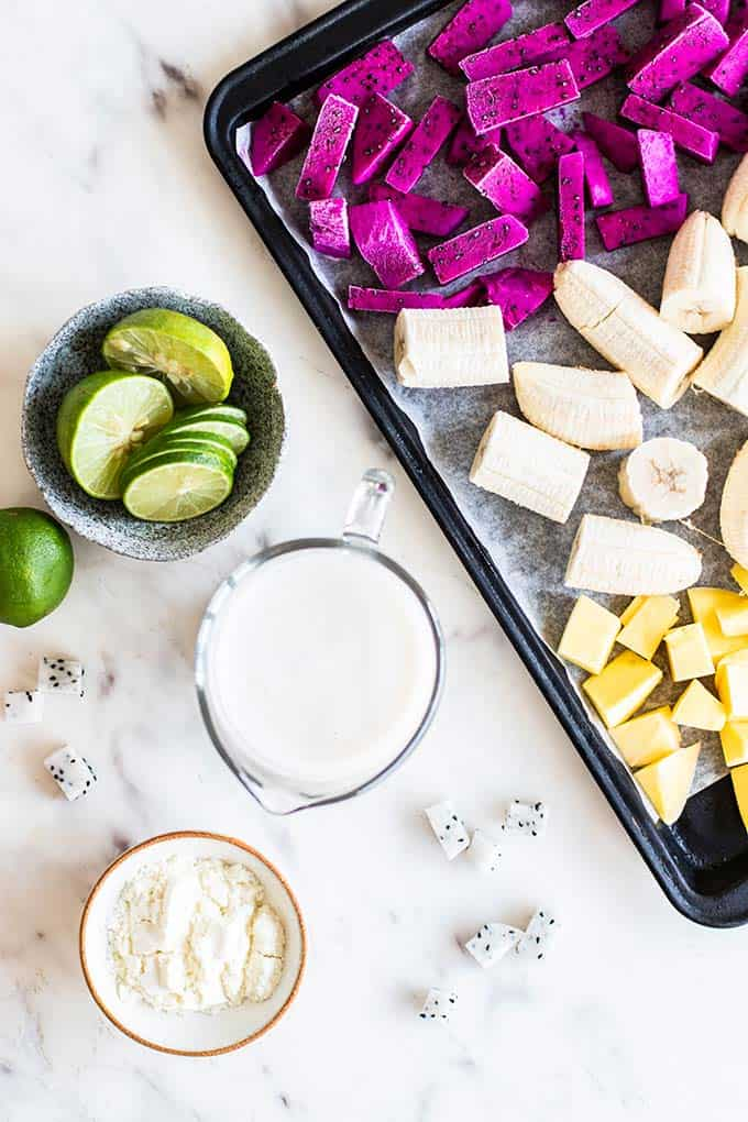A tray of frozen dragon fruit, mango and bananas, with limes, almond milk and whey protein powder set to the side,