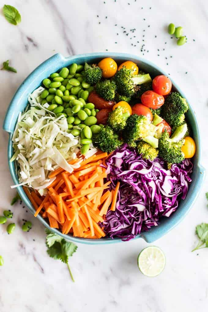 A blue dish filled with colorful vegetables, prepared for a salad.