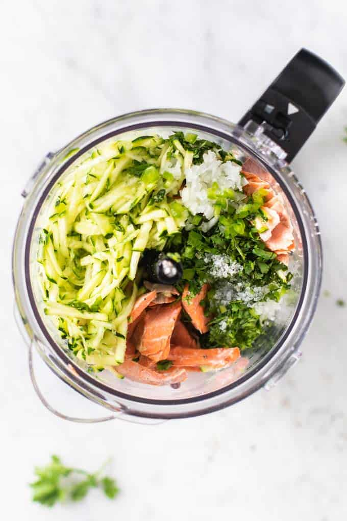 A food processor bowl filled with salmon, zucchini, cilantro, onions, jalapenos and eggs.