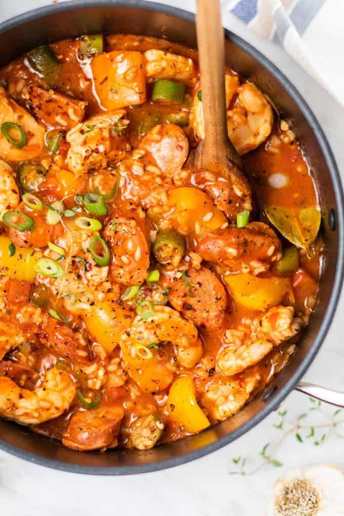 A close up of a pot of Jambalaya with a wooden spoon.