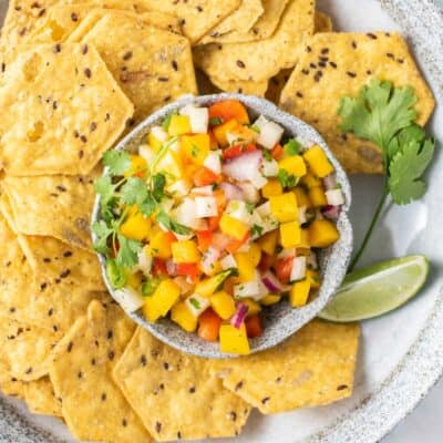 A bowl of multi grain chips with a dish or mango salsa garnished with limes and cilantro.