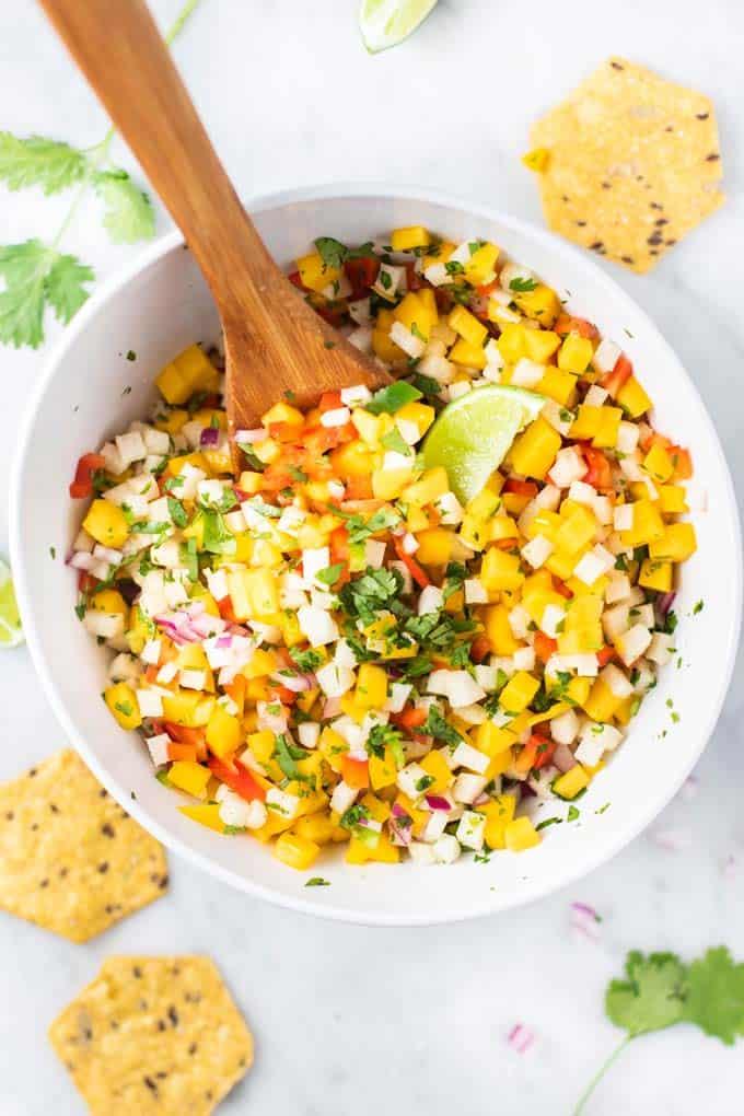 A large white bowl showing how to make a batch of mango jicama salsa.